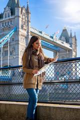 Attraktive Touristin schaut auf eine Stadtkarte vor der Tower Bridge während ihres Städtetrips nach London, Großbritannien