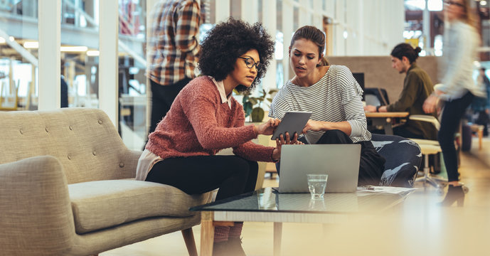 Female coworkers discussing work in office