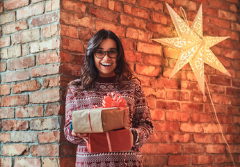 Portrait of a cheerful brunette girl wearing glasses and a warm sweater holding gift boxes while leaning on a brick wall.