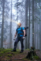 Man with headlamp and backpack in the forest