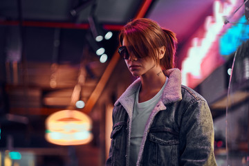 Stylish redhead girl standing in the night on the street. Fotomurales
