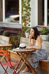 Beautiful Lady With A Hat Sitting On A Summer Terrace