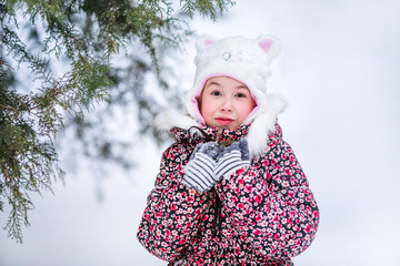 Smiling girl with white fur hat like a cat. Winter snowy background and gteen trees