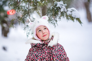 Portrait of smiling girl with white fur hat like a cat. Winter snowy background and gteen trees
