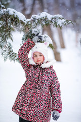Smiling girl with white fur hat like a cat playing with snow. Winter snowy background and gteen trees