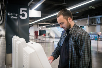 Young man using self check-in kiosks in airport.