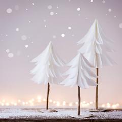 Winterliche Weihnachtsdekoration mit kleinen Tannenbäumen aus Papier und Lichterbokeh im Hintergrund