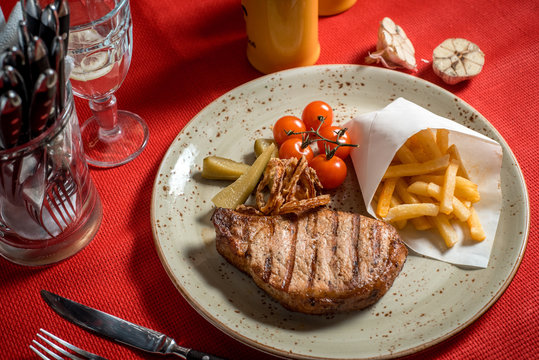 Grilled New York strip steak with bearnaise sauce, potato wedges, and cherry truss tomatoes. Garnished with parsley and rosemary.