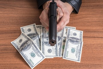 Robbery concept. Man is holding gun in hands and stealing money.