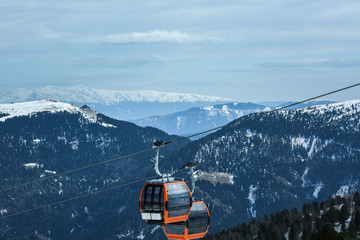 Orange gondola cabins of cableway lift on winter snowy mountains background beautiful scenery