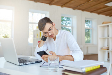Indoor shot of concentrated tired young businessman wears white shirt and glasses using laptop and cell phone sitting and working at the table in office
