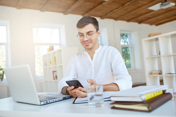 Closeup of smiling attractive young businessman wears white shirt and glasses with laptop and mobile phone feels happy and working at the table in office