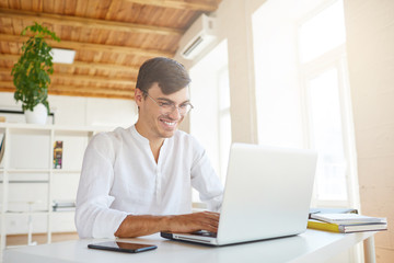Portrait of cheeful confident young businessman wears white shirt and spectacles using laptop and smartphone working at the table in office and laughing