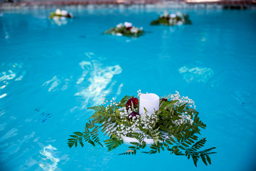 Flowers and candles floating in the pool