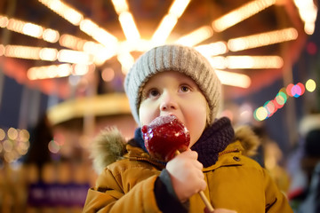 Little boy eating red apple covered in caramel on Christmas market. Traditional child's enjoyment and fun during Xmas time.