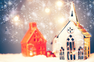 Christmas village made with different candle house, snow, blue background, and beautful bokeh and effect adding mood to the photo, space for adding your text.