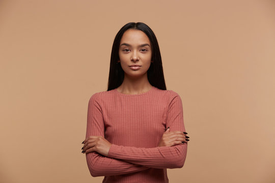 Portrait of calm, confident, attractive young mixed race brunette girl stands with arms crossed, dressed casual, on beige background