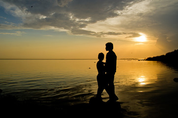 couple of people on the beach in the light of the sunset are about calm water