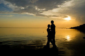 couple of lovers on the shore admires the sunset over the water