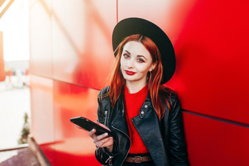Fashion smiling woman is using smartphone on a red background