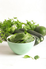 Fresh green vegetables in a bowl and on the white table