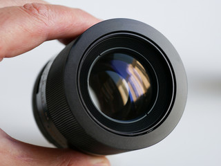 Black camera lens in a man's hand closeup, showing the front element with reflections on the clean class.