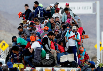 Migrants, part of a caravan of thousands traveling from Central America en route to the United States, sit on the back of a truck while making their way to Tijuana from Mexicali, in Mexicali