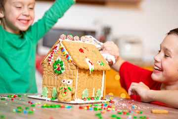 children having fun decorating the gingerbread house. the concept of family preparing to Christmas. selective focus