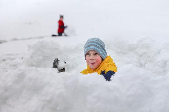 snow fight. joyful boy throws snowballs from a snow fortress