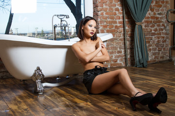 Girl with naked breasts sitting on the floor by the bath