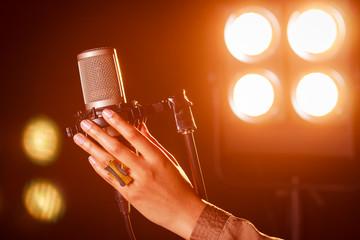 Mano de mujer sujetando un micrófono