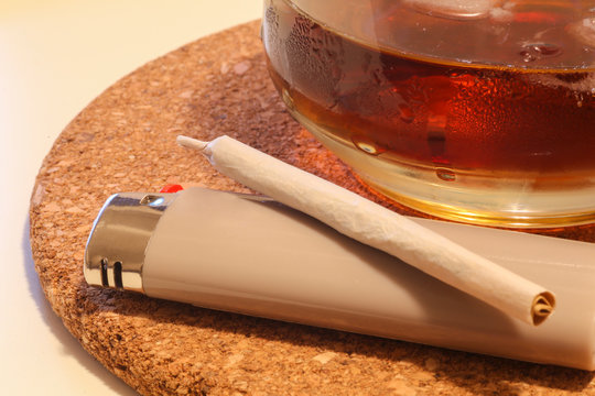 Close-up of a pot cigaret and a drink on the table. Relax time VS Addiction issue