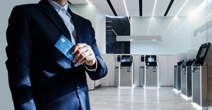 Bank manager with credit card in hand, business man standing confidently with pride in modern financial, futuristic, technology and banking network connection