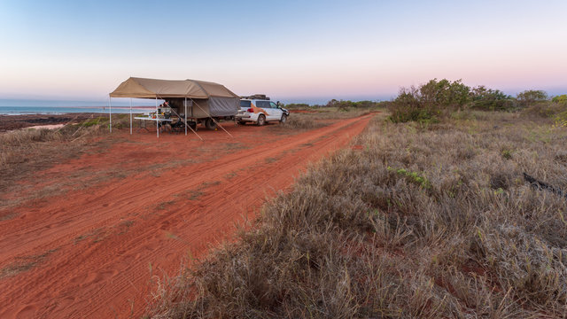 Offroad camper trailer and four wheel drive vehicle camping on top of the red cliffs at James Price Point in the Kimberley Region od Western Australia.