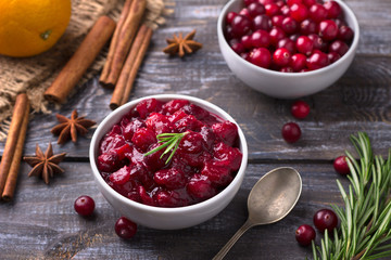 Homemade spicy cranberry sauce with fresh cranberries, cinnamon and star anise on a wooden background