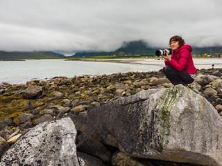 Tourist with camera on Skagsanden Beach Lofoten Norway