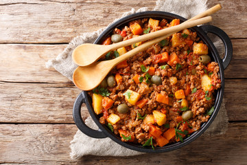 Delicious Picadillo cooked from ground beef with vegetables, raisins and spices close-up in a frying pan. horizontal top view