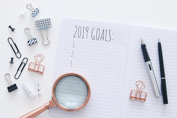 Top view 2019 goals list with notebook over white wooden desk.