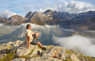 Resting tourist on the stony ridge with mountains on backround, Pyrenees