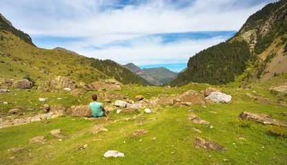 Resting tourist on the stony meadow in the mountain valley, Pyrenees