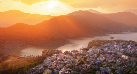 he sunset sky above the city of Pokhara and Phewa lake with World Peace Pagoda on the top of hill. Nepal