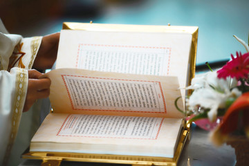 The Book of the Gospel is open for reading in the hands of the priest at the wedding