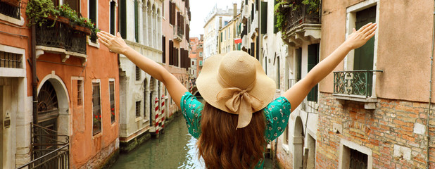 Europe travel vacation fun summer woman with arms up and hat happy in Venice, Italy. Panoramic banner view of carefree girl tourist in European destination wearing green fashion dress.