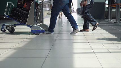 Unrecognizable people with baggages walking in terminal airport