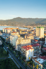 Batumi, Adjara, Georgia - October 2018: cityscape seen from the top of Sheraton sky bar during sunset golden hour with mountains in background