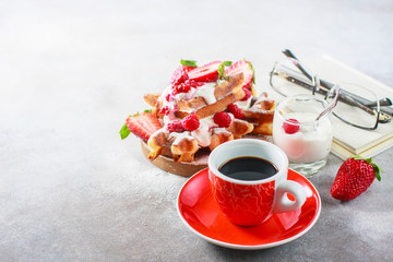 Belgian waffles with creem, raspberries, strawberriesand coffee , top view with copy space.