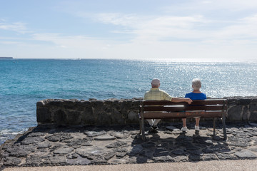 Elderly couple looks at the sea and sitting on a bench. Travel in old age