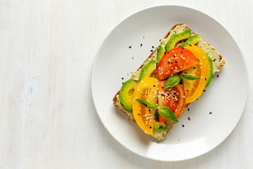 Avocado and tomato toast on plate with copy space
