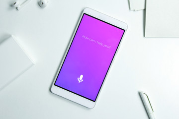 Personal assistant and voice recognition concept on smartphone over white table. Microphone button and how can I help you text.