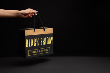 partial view of woman holding black shopping bag with black friday sale - start shopping